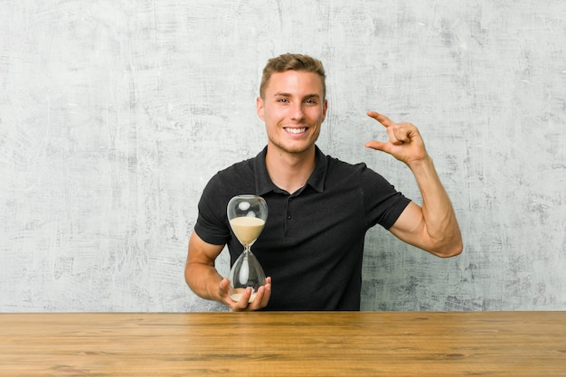 Young man holding a sand timer on a table holding something little with forefingers, smiling and confident.