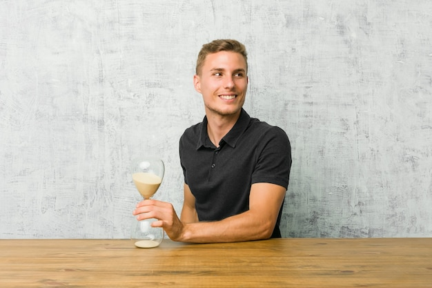 Young man holding a sand timer on a table looks aside smiling, cheerful and pleasant.