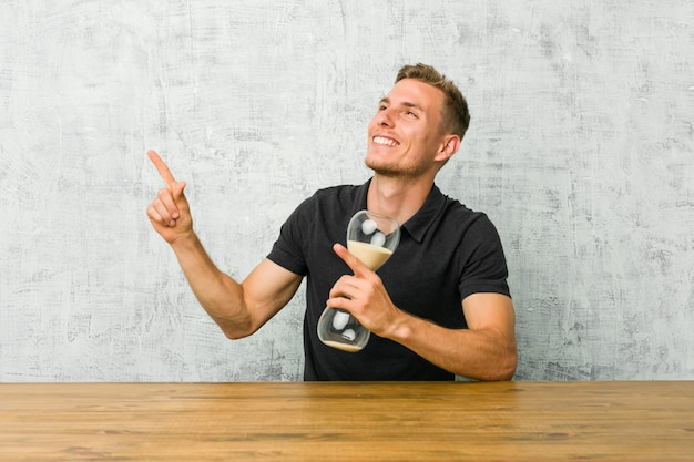 Young man holding a sand timer on a table pointing with forefingers to a copy space, expressing excitement and desire.