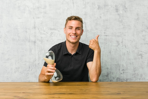 Young man holding a sand timer on a table raising both thumbs up, smiling and confident