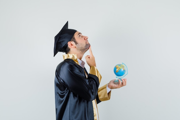 Young man holding school globe in graduate uniform and looking pensive .