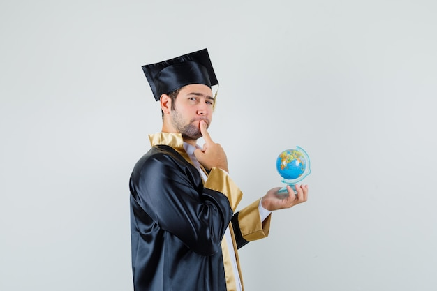 Young man holding school globe in graduate uniform and looking thoughtful .
