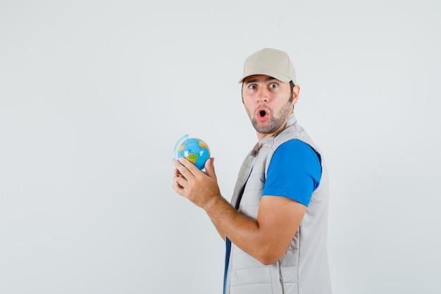 T- 셔츠, 재킷에 학교 글로브를 들고 놀 찾고 젊은 남자.