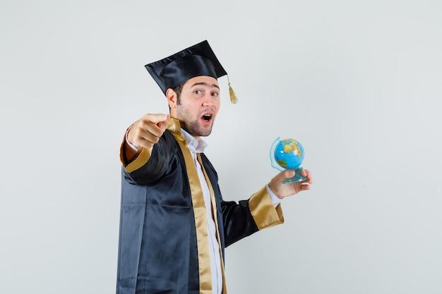Globo della scuola della holding del giovane, indicante alla macchina fotografica in uniforme laureato, vista frontale.