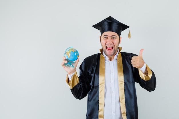 Giovane che tiene il globo della scuola, che mostra il pollice in su in uniforme laureato e che sembra fortunato, vista frontale.