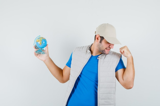 Young man holding school globe in t-shirt, jacket and looking blissful , front view.