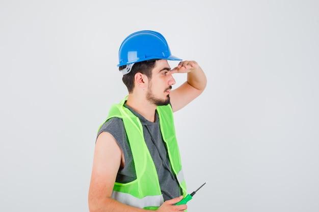 젊은 남자가 드라이버를 들고 건설 유니폼을 멀리보고 심각한 찾고