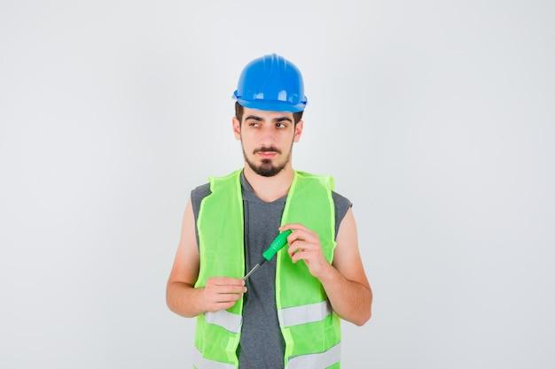 드라이버를 들고 젊은 남자, 건설 유니폼을 멀리보고 잠겨있는 찾고