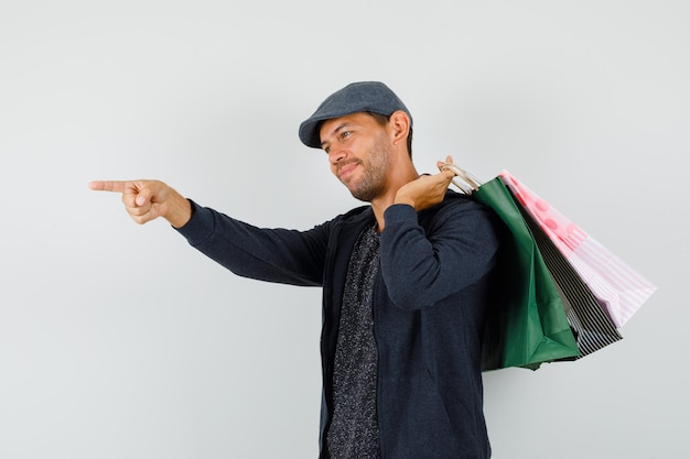 Young man holding shopping bags, pointing away in t-shirt, jacket, cap and looking optimistic