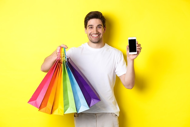 Young man holding shopping bags and showing mobile phone screen, money application, standing over yellow background