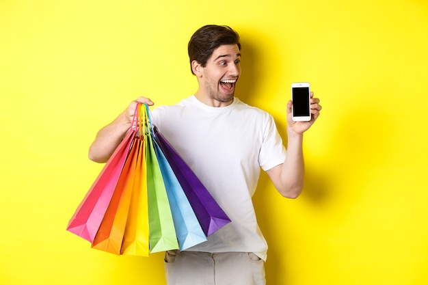 Young man holding shopping bags and showing mobile phone screen, money application, standing over yellow wall
