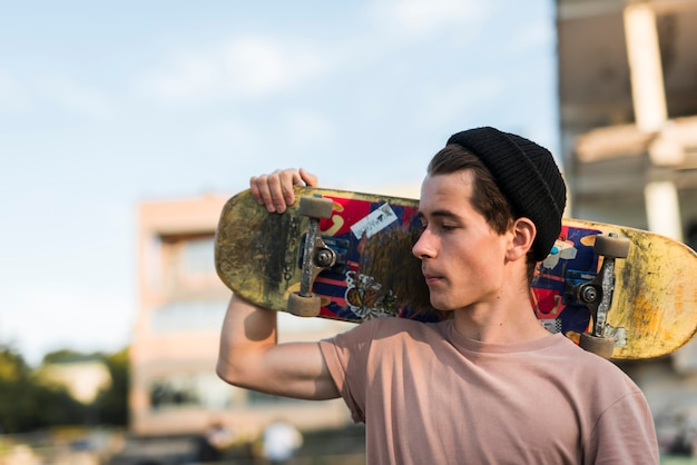Young man holding a skateboard