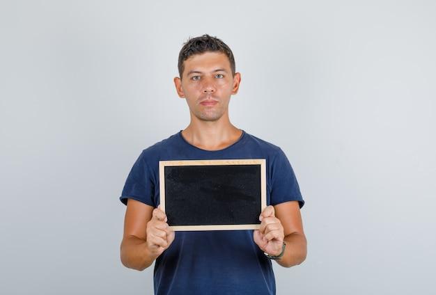 ダークブルーのtシャツに小さな黒板を保持していると深刻な若い男。正面図。