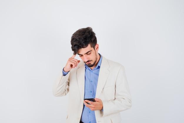 젊은 남자가 스마트 폰을 들고 파란색 티셔츠와 흰색 정장 재킷에 귀에 검지 손가락을 넣고 심각한 찾고