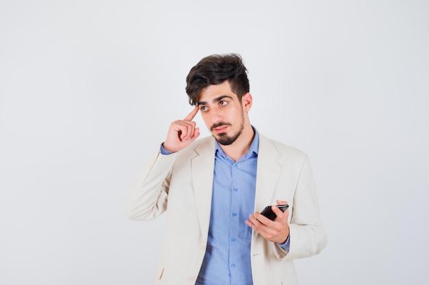 スマートフォンを持って、青いtシャツと白いスーツのジャケットでポーズを考えて立って物思いにふける若い男
