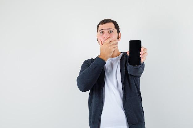 スマートフォンを持って、白いtシャツとジップフロントの黒いパーカーで口を手で覆って驚いた若い男。正面図。
