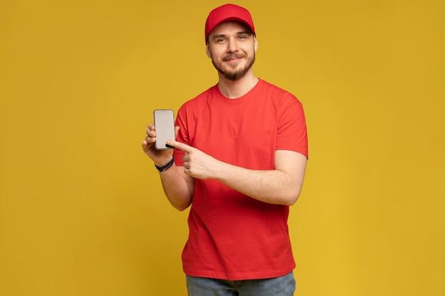 黄色の壁に分離されたスマートフォンを保持している若い男