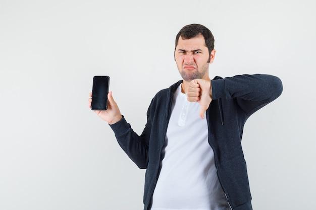 スマートフォンを持って、白いtシャツとジップフロントの黒いパーカーで親指を下に見せて、不機嫌そうに見える若い男、正面図。