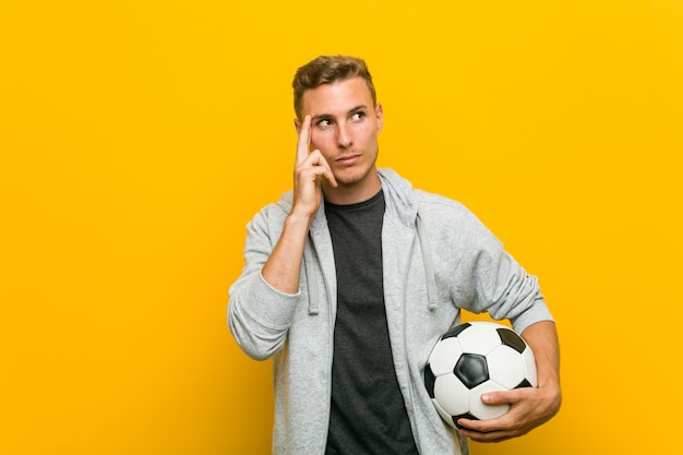 Young man holding a soccer ball pointing his temple with finger, thinking, focused on a task