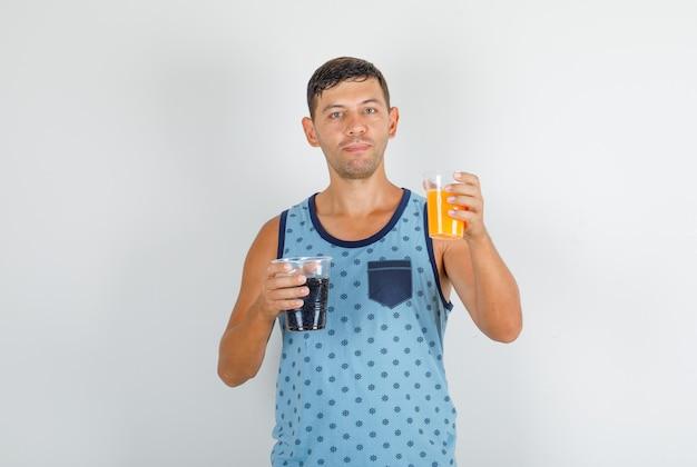 青い一重項で清涼飲料を保持している若い男