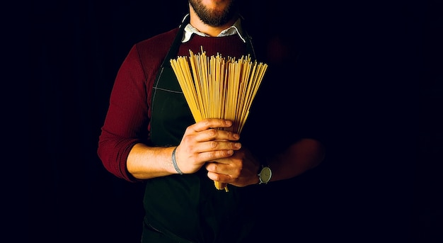 Young man holding spaghetti pasta with apron on