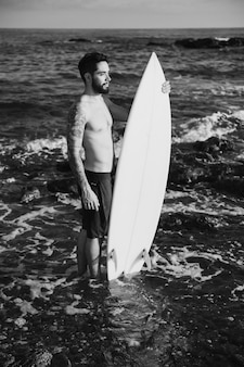 Young man holding surf board in water