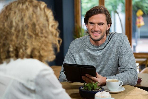 コーヒーショップで女性を見ながらタブレットpcを保持している若い男