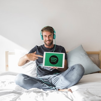 Young man holding tablet with spotify app