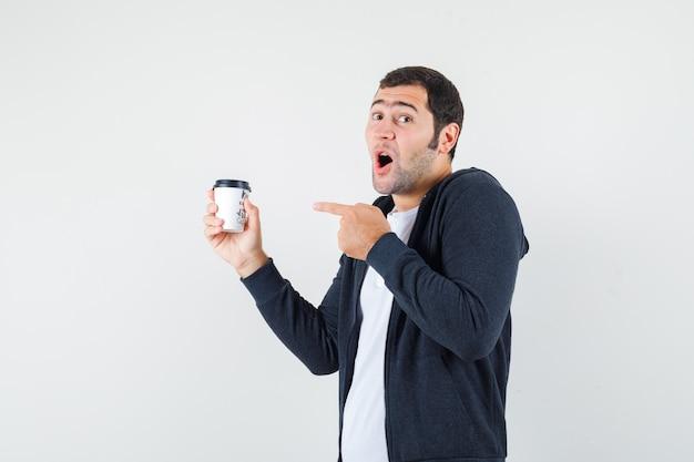 테이크 아웃 커피 컵을 들고 흰색 티셔츠와 지퍼 앞 검은 까마귀에 검지 손가락으로 가리키고 놀란, 전면보기를 보는 젊은 남자.