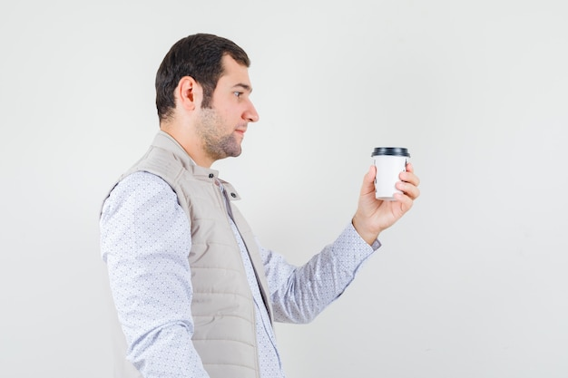Young man holding takeaway cup of coffee and looking at it in beige jacket and looking serious , front view.