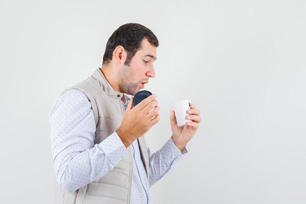 Young man holding takeaway cup of coffee and trying to open it in beige jacket and looking focused. front view.