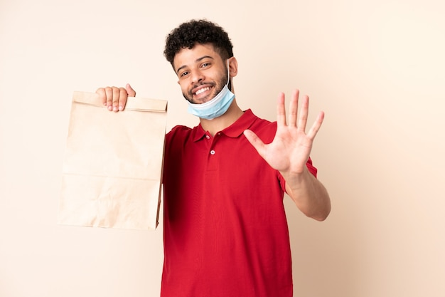 Young man holding a takeaway food bag ___ saluting with hand with happy expression