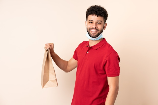Young man holding a takeaway food bag ___ smiling a lot