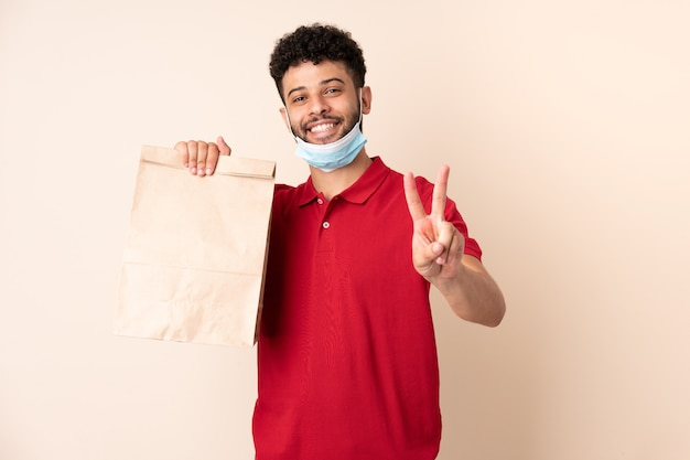 Young man holding a takeaway food bag ___ smiling and showing victory sign