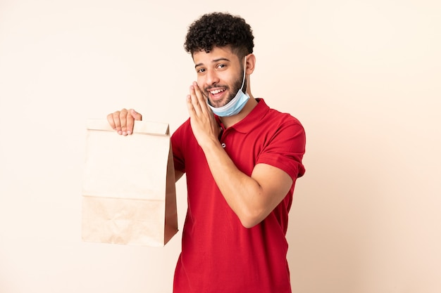Young man holding a takeaway food bag ___ whispering something