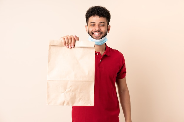 Young man holding a takeaway food bag ___ with happy expression