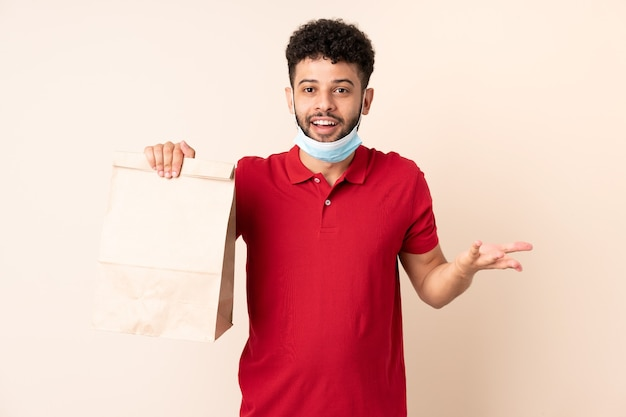 Young man holding a takeaway food bag ___ with shocked facial expression