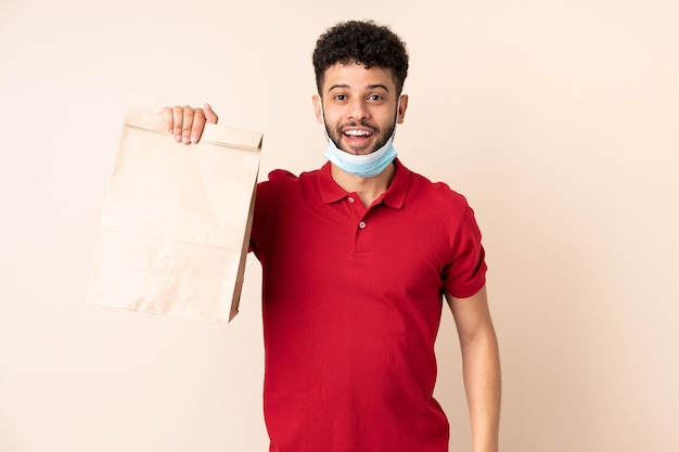 Young man holding a takeaway food bag with surprise and shocked facial expression
