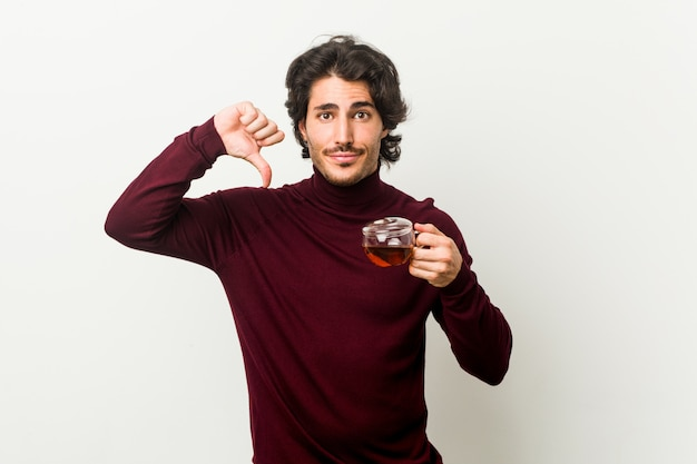 Young man holding a tea cup showing a dislike gesture, thumbs down. disagreement concept.