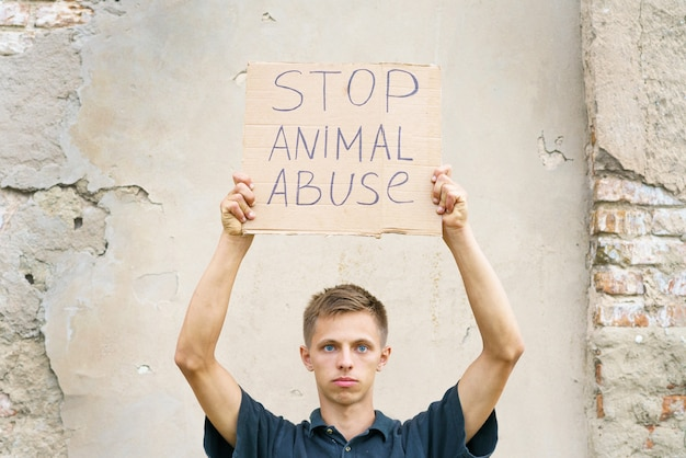 Молодой человек держит в руках надпись «остановить жестокое обращение с животными» Premium Фотографии