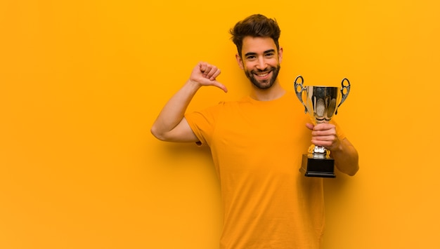 Young man holding a trophy pointing fingers, example to follow