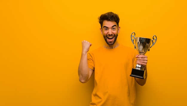 Young man holding a trophy surprised and shocked