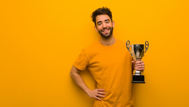 Young man holding a trophy with hands on hips