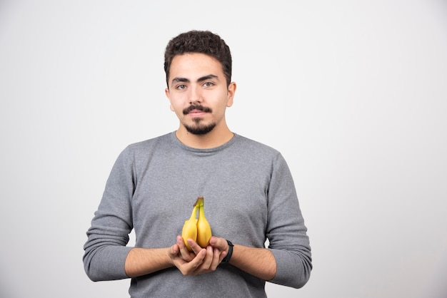 A young man holding two fresh bananas .
