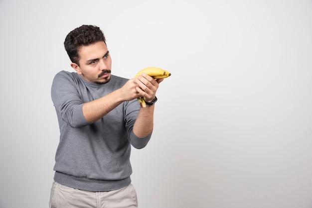 Un giovane che tiene due banane fresche.