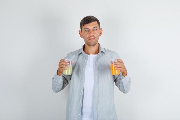 Молодой человек, держащий два стакана сока в вид спереди рубашку.