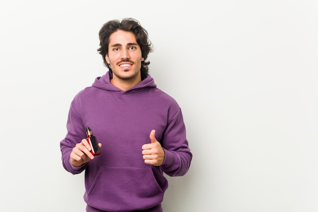Young man holding a vaporizer smiling and raising thumb up