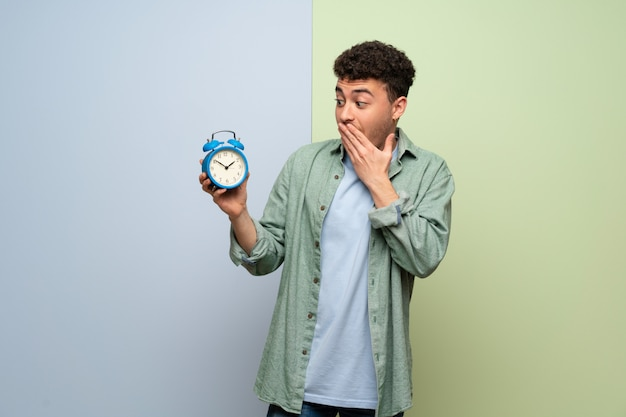 Young man holding vintage alarm clock