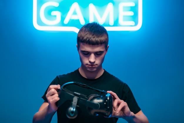 Vrメガネを保持している若い男。ストラットゲーム。