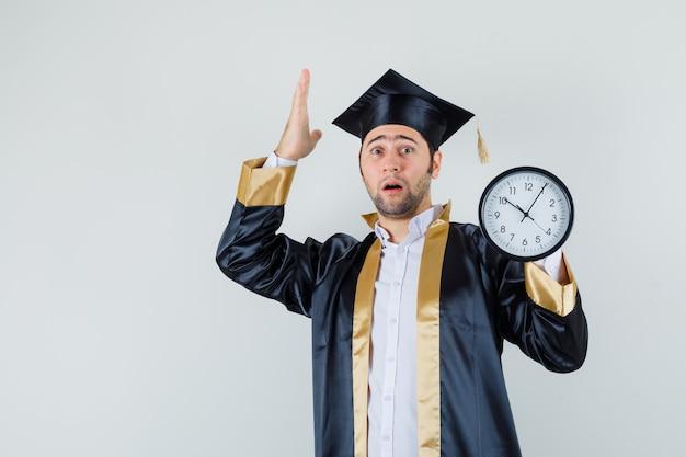 Giovane uomo con orologio da parete in uniforme laureato e guardando impotente, vista frontale.